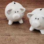Two White Piggy Banks on Floor